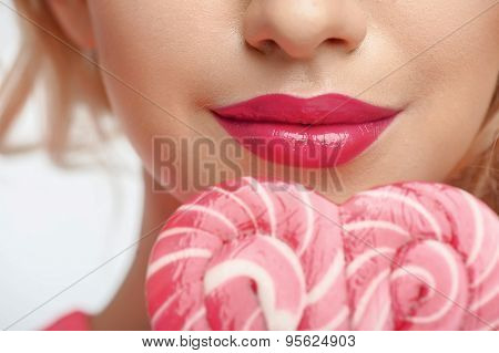 Beautiful young woman with sweet pink candy