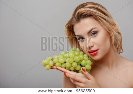 Attractive young woman is holding green grape