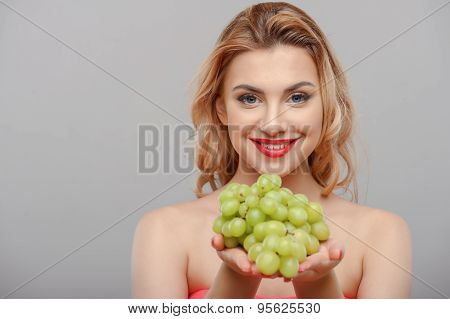 Cheerful young girl is presenting fresh green fruit