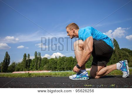 Cheerful young sportsman is preparing before running