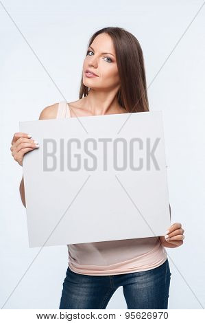 Beautiful young girl is presenting white frame