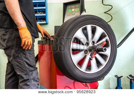 Mechanic Balancing A Car Wheel