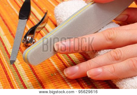 Woman Polishing Fingernails With Nail File