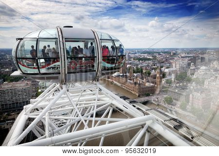 LONDON - JUNE 25: View from the London Eye capsule from its highest point on June 25 2015 in London, UK. People admiring the bird's eye view on Big Ben and River Thames.
