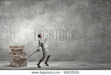 Young businesswoman with ropes on hands pulling pile of books