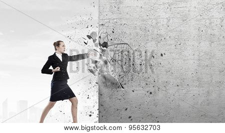 Businesswoman breaking stone wall with karate punch