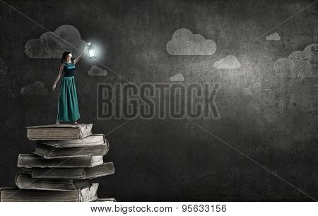 Young woman in green dress with lantern standing on pile of books