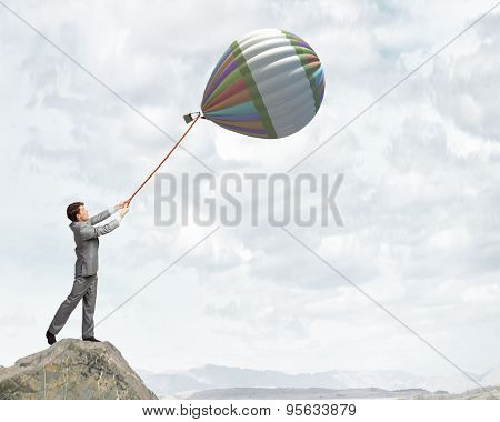 Young businessman caught colorful balloon on lead