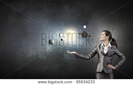 Young businesswoman exploring planets of sun system