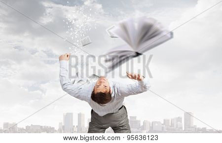 Businessman bent over and evading from book