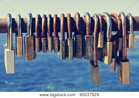 closeup of a lot of rusty padlocks locked in the crossbar of a rusty railing near the sea