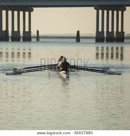 skulls rowing team rowing on open water with bridge in background