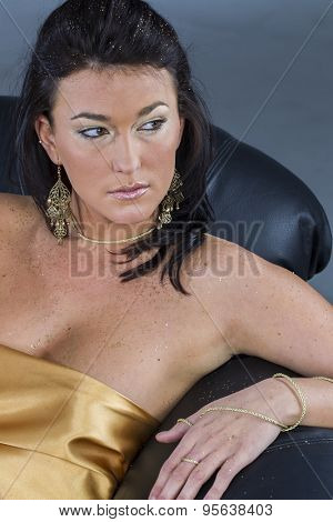A brunette model poses on a sofa in a studio environment