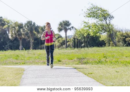 A brunette woman jogs along the beach on a sunny day