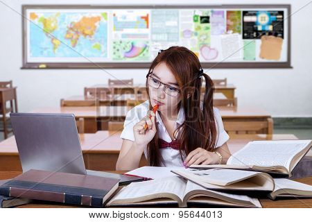Brunette Student Studying On Desk In Class