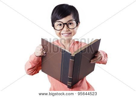 Cute Child Reading Book In Studio