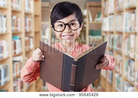 Lovely Child With Glasses Holding Book In Library