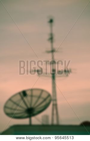 Blurred Tv Satellite Dishes And Antennas On Roof At Sunset.