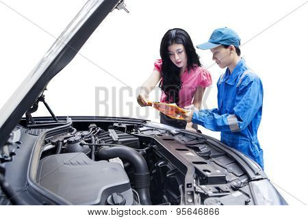 Woman With Mechanic Looking At Clipboard