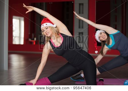 Two Pretty Girls In Santa Claus Hats Do Body Bending On Mats In Fitness Center