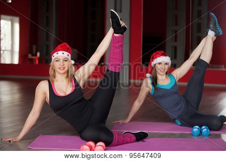 Two Pretty Girls In Santa Claus Hats Stretching Legs On Mats In Fitness Center