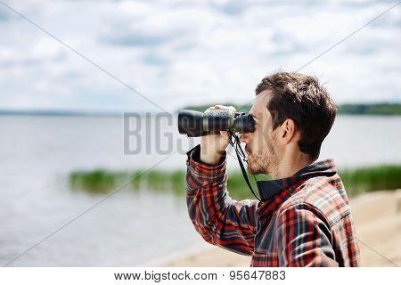 Man Looks Through Binoculars While Fishing At The Lake On Vacation
