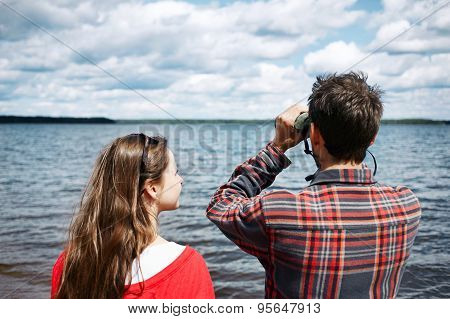 Close Up Portrait Back Of Men And Women Looks Through Binoculars While Fishing On Vacation With Lake
