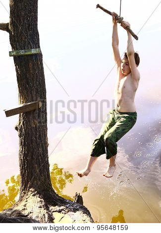 preteen boy  with water swing on vacation