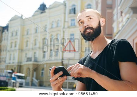 Attractive young bearded man got lost in city