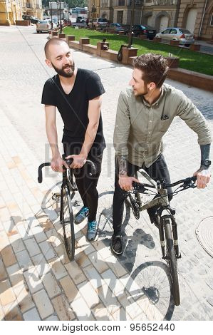 Attractive young hipster guys are cycling in city
