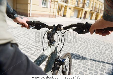 Young man with tattoo is cycling in city