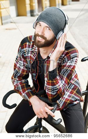 Handsome styled hipster guy is sitting on bicycle