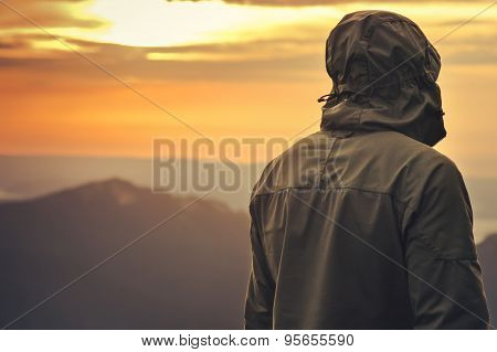 Young Man standing alone outdoor with sunset mountains on background