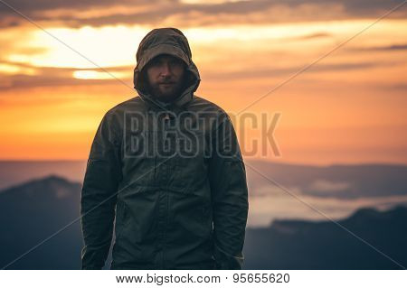 Man Traveler bearded standing alone outdoor with sunset mountains on background