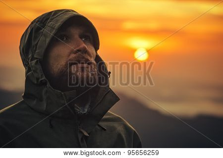 Man Traveler bearded face alone outdoor with sunset mountains on background