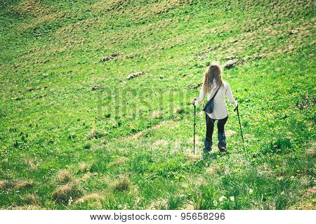 Young Woman with trekking poles hiking outdoor Travel