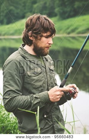 Young Man Fisherman bearded standing with rod