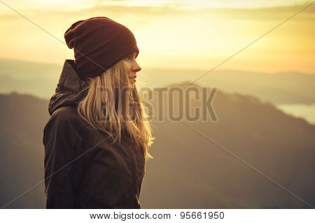Young Woman standing alone outdoor with sunset mountains on background