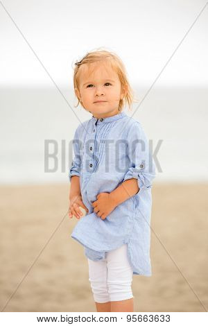Cute curious little girl at the beach standing on the golden sand clutching her dress and looking at the camera with a tentative smile