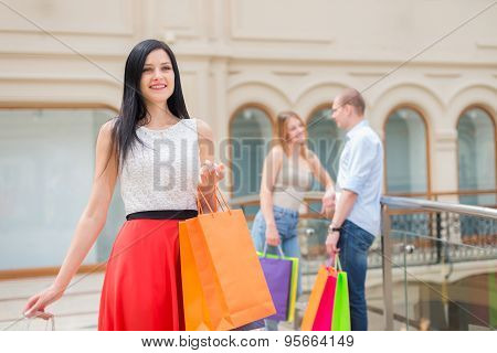 Smiling Girls And A Man With Shopping Bags In A Luxury Central Shop. Shopping, Sale, Gifts And Holid