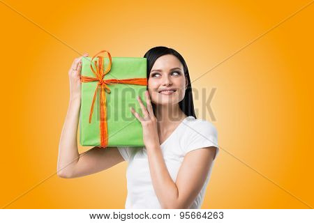 A Brunette Woman Is Holding A Green Gift Box. Orange Background.