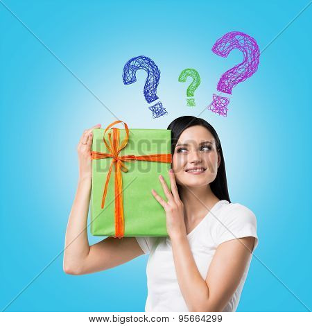 A Brunette Woman Is Holding A Green Gift Box And Question Mark As A Concept Of Gift Uncertainty. Blu