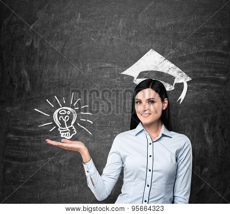 Brunette Lady Presents A Light Bulb As A Concept Of University Degree. Graduation Hat Is Drawn Above