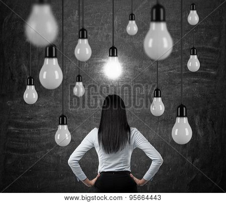 Rear View Of The Brunette Lady Who Is Looking At The Hanging Light Bulbs. A Concept Of Searching New