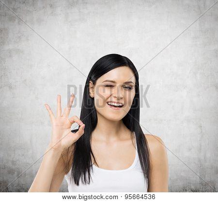 Brunette Woman Shows Ok Sign. Concrete Background.