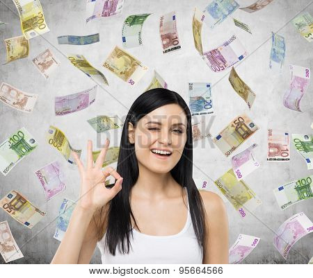 Brunette Woman Shows Ok Sign. Euro Notes Are Falling Down Over Concrete Background.