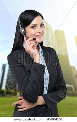 Portrait Of Brunette Support Phone Operator With The Headset. Business Skyscrapers On The Background