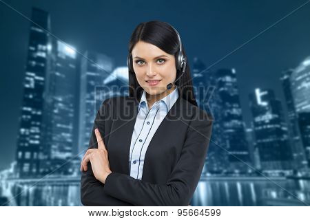 Portrait Of Brunette Support Phone Operator With The Headset. Business Evening Area Of Singapore On