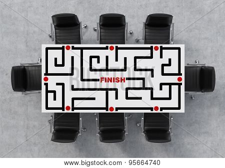 Top View Of A Conference Room. A White Rectangular Table And Eight Black Chairs Around. A Labyrinth