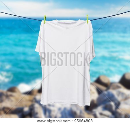 Close Up Of A White T-shirt On The Rope. Sea And Rocks In A Blur As A Background.